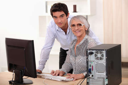 Young man and older woman using a computer photo