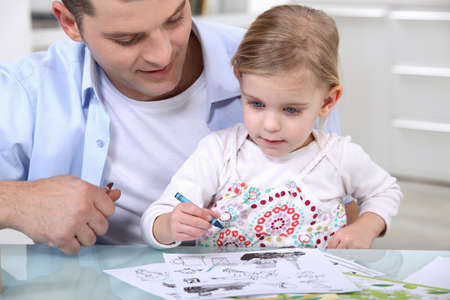 Little girl drawing with father photo