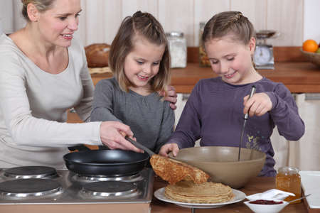 Woman cooking crepes with her daughters photo