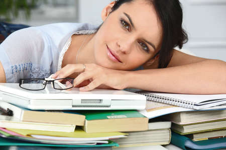 unmotivated: Tired student leaning on a pile of books