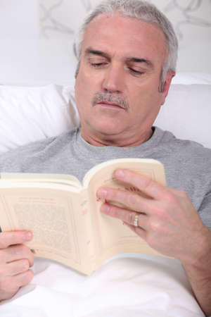 45 to 50 years old: Mature man reading book in bed