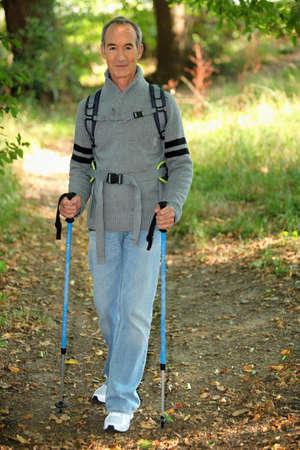 senior gentleman in forest with rambler walking poles photo