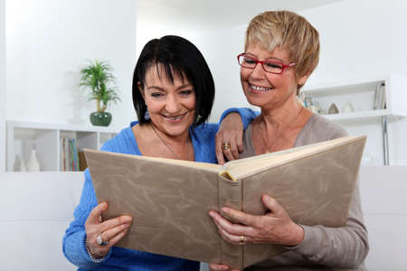 wistfulness: Two women looking through photo album Stock Photo