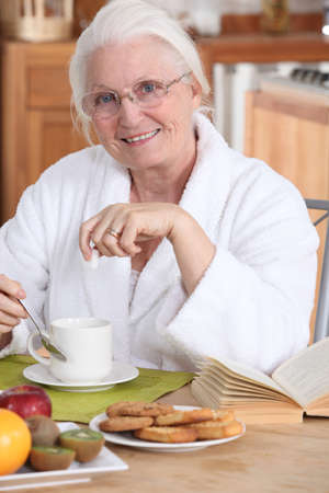 Old lady eating breakfast Stock Photo - 10853338