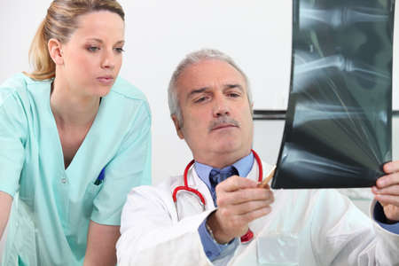 electromagnetic radiation: Doctor and his assistant looking at an x-ray