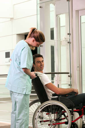 Nurse and patient in wheelchair in front of a lift photo