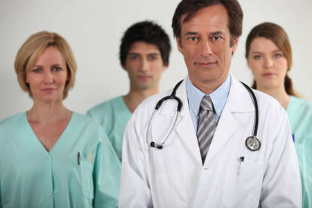 A doctor and three nurses behind him, all looking at us. Stock Photo - 10854241