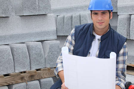 Construction worker standing next to pallets of concrete curb while looking at some plans photo