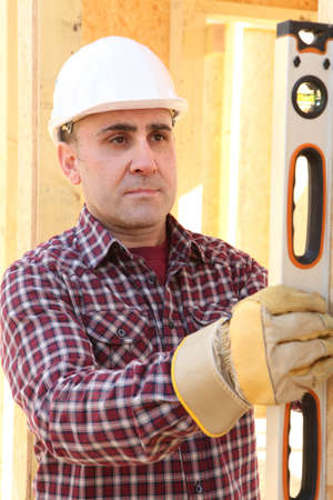 poker faced: Construction worker using a spirit level