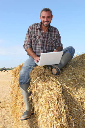 40 years old man: farmer seated on straw bale and doing computer