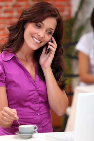 auburn hair: Woman on a cellphone while stirring an expresso in a restaurant Stock Photo