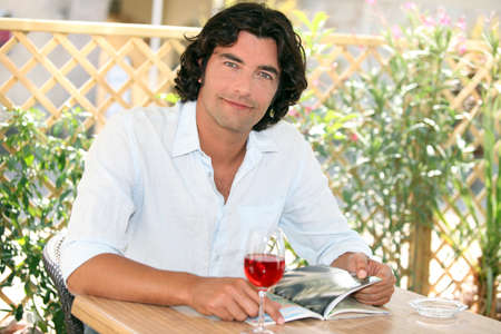 Man enjoying a glass of wine at an outdoor cafe photo