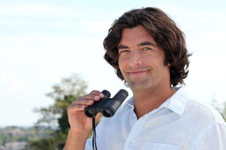 look pleased: Man with binoculars Stock Photo