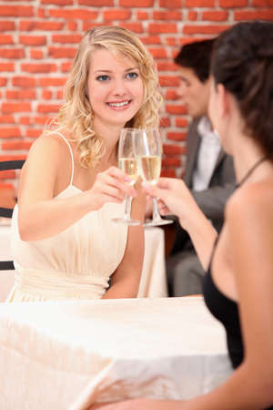 Girls drinking champagne in a restaurant photo