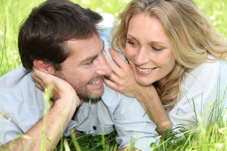 Happy couple lying on grass photo