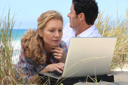 Wife working on laptop on the beach. Stock Photo - 10855025