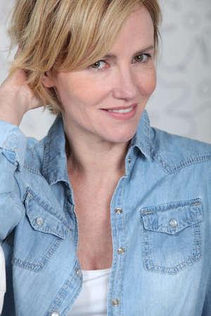 wry: Closeup of woman in a denim shirt