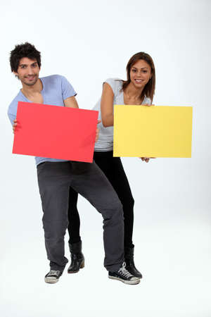 a young man and a young woman calling attention by showing panels Stock Photo - 10852175