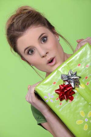 hair tied: Pretty girl holding gift on green background
