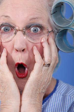 hair rollers: Se�ora de edad sorprendido usando rulos Foto de archivo