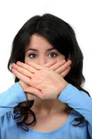 vrouw die haar mond met haar handen Stockfoto