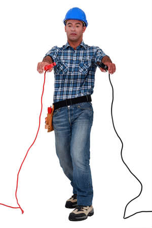 Tradesman holding jumper cables Stock Photo - 10852294