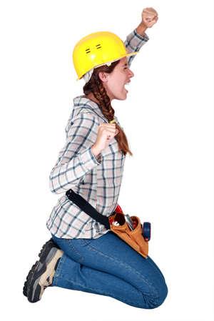 kneeling woman: craftswoman kneeling and stretching Stock Photo
