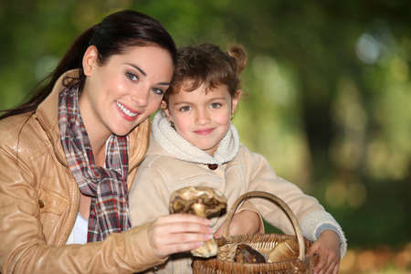 Young woman and little girl picking mushrooms in the countryside Stock Photo - 10854484