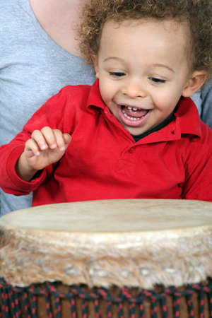 Little boy playing with djembe photo