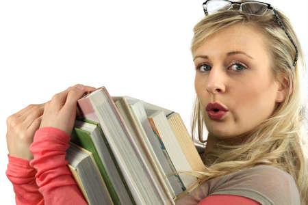 pile of books: Giovane donna con una pila di libri tra le braccia Archivio Fotografico