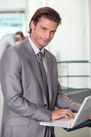 man in suite: Businessman typing on laptop computer