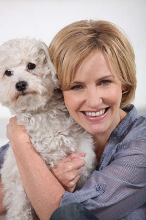 Smiling woman with small white dog