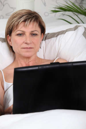 Mature woman using a laptop in bed Stock Photo - 10853657
