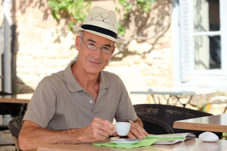 village man: senior citizen sipping his coffee in terrace cafe