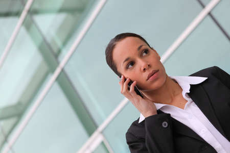 reachable: businesswoman making call near office Stock Photo