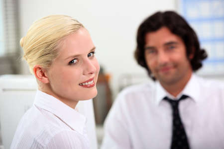 subordinated: Smiling woman sitting with a colleague Stock Photo