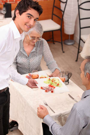 courteous: Waiter serving a meal Stock Photo