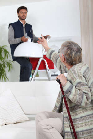 Young man putting up a light for an elderly woman photo