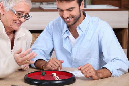 aide � la personne: jeune homme jouant aux d�s avec femme plus �g�e