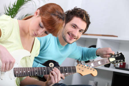 a guitar teacher and his female student photo