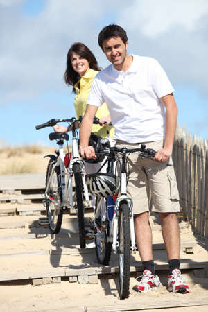 Couple taking their bikes to the beach photo
