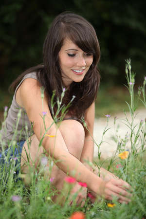 Young woman picking wildflowers from the side of a pathway Stock Photo - 10855225