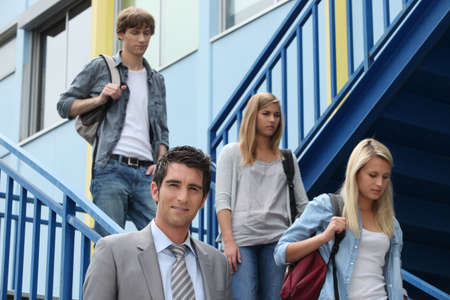college building: Three students walking down stairs alongside teacher Stock Photo