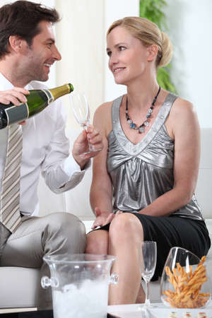 smartly: Two smartly dressed people about to drink champagne.