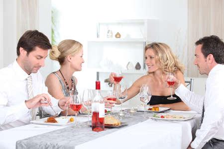 fiesta familiar: Dos parejas que disfrutan de comer juntos