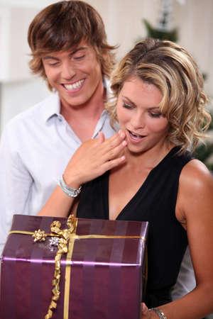 Young man giving his girlfriend a Christmas present Standard-Bild