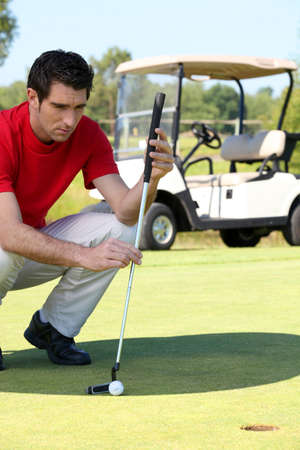 Golfer crouched next to the hole photo