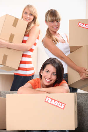 marked: Three young women moving cardboard packing boxes marked fragile