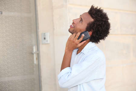 intercom: a man at phone in front of a closed door Stock Photo