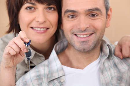 Mature couple holding up a set of keys photo